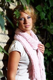 Jeune femme à côté d'un mur de briques