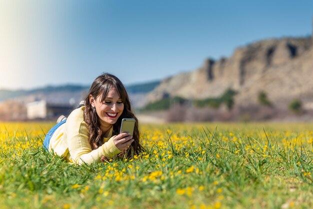 Jeune femme couchée à l'aide d'un téléphone portable