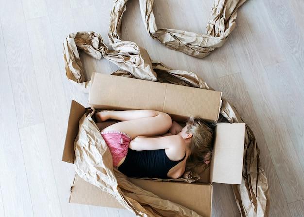 Jeune femme couchée dans une boîte en carton en pose d'embryon