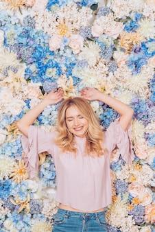 Jeune femme couchée sur des fleurs aux couleurs vives