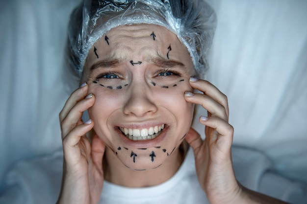 Jeune femme, coucher divan, dans, casquette, et, pleurer. elle souffre de douleur. le modèle touche son visage. c'est marqué.