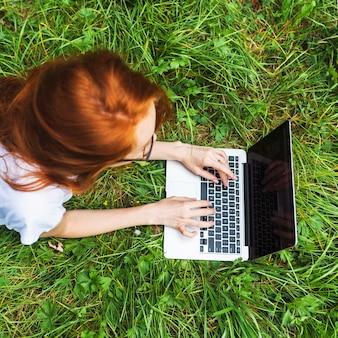 Jeune femme, coucher herbe, à, ordinateur portable