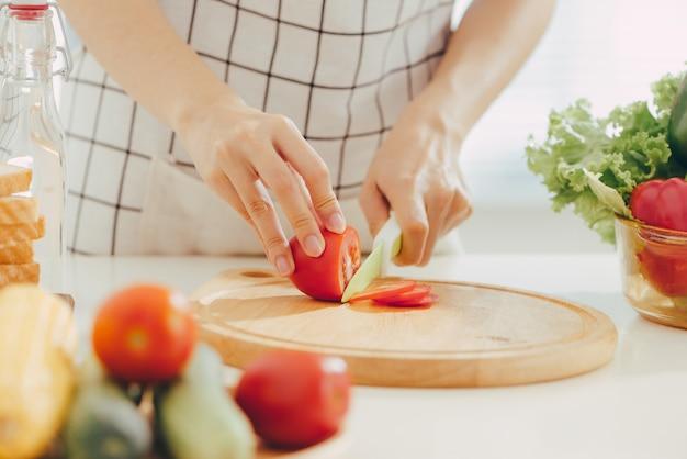 Jeune femme coupant des légumes dans la cuisine