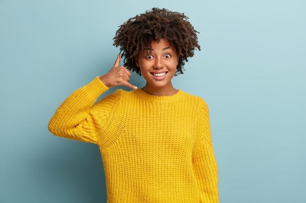 Jeune femme avec coupe de cheveux afro portant un pull jaune