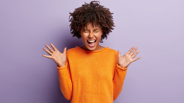 Jeune femme avec coupe de cheveux afro portant un pull orange