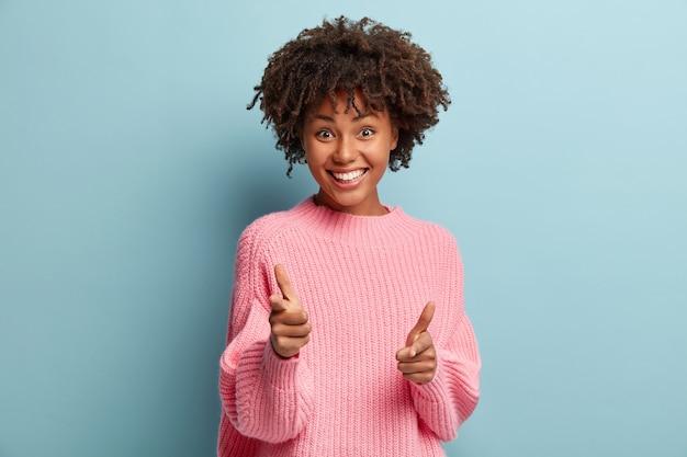 Jeune femme avec coupe de cheveux afro portant un pull rose