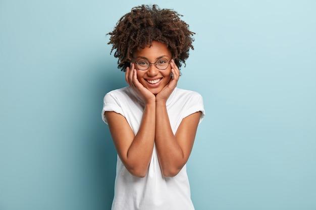 Jeune femme avec coupe de cheveux afro portant un t-shirt blanc