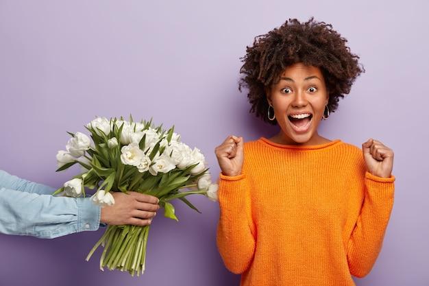 Jeune femme avec coupe de cheveux afro recevant un bouquet de fleurs