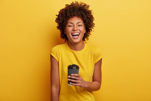 Jeune femme avec coupe de cheveux afro et t-shirt jaune tenant une tasse de café