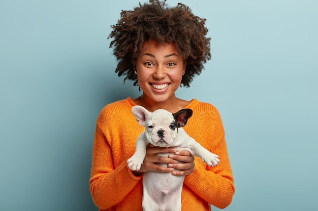Jeune femme avec coupe de cheveux afro tenant chiot