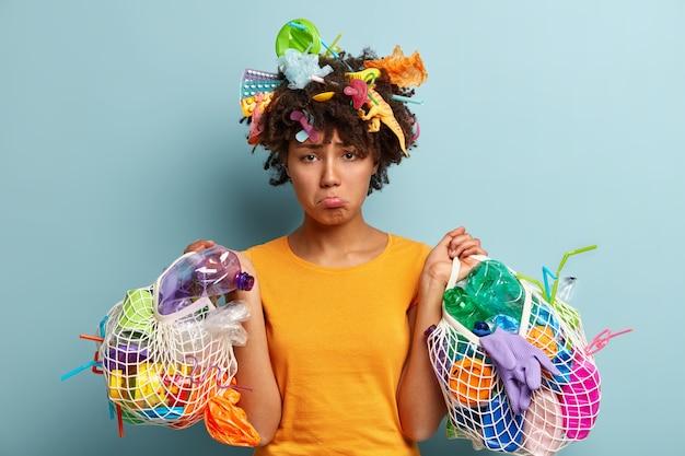 Jeune femme avec coupe de cheveux afro tenant un sac avec des déchets plastiques