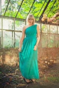Jeune femme avec coupe de cheveux bob en robe de soirée turquoise sur une épaule est debout dans une serre abandonnée en automne. séance photo mise en scène - poubelle la robe