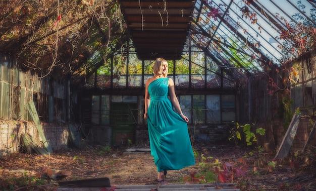 Jeune femme avec coupe de cheveux bob en robe de soirée turquoise sur une épaule est debout dans une serre abandonnée en automne