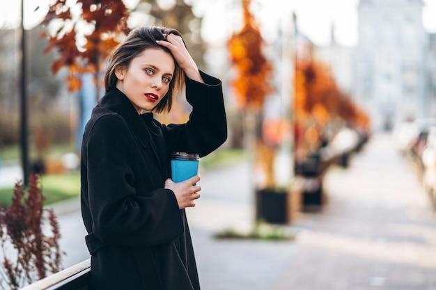 Jeune femme à la coupe courte et aux lèvres rouges, tient une tasse de café, se promenant dans les rues de la ville. autour se trouvent des gens et des voitures.