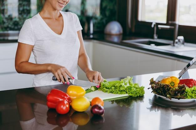 La jeune femme coupe des légumes dans la cuisine avec un couteau