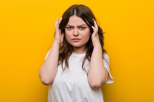 Jeune femme courbée taille plus concentrée sur une tâche, lui gardant l'index pointé de la tête.