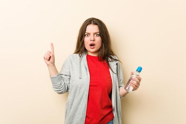 Jeune femme courbée taille plus tenant une bouteille d'eau ayant une excellente idée, concept de créativité.