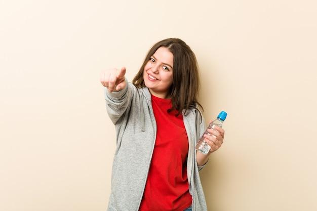 Jeune femme courbée taille plus tenant une bouteille d'eau sourires joyeux pointant vers l'avant.