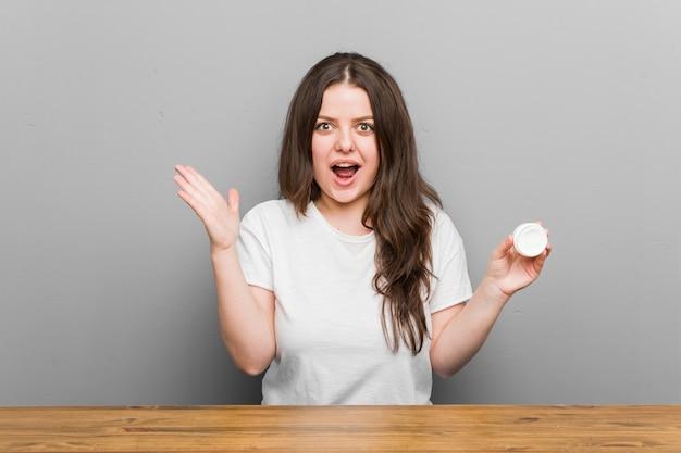 Jeune femme courbée taille plus tenant une crème hydratante célébrant une victoire ou un succès