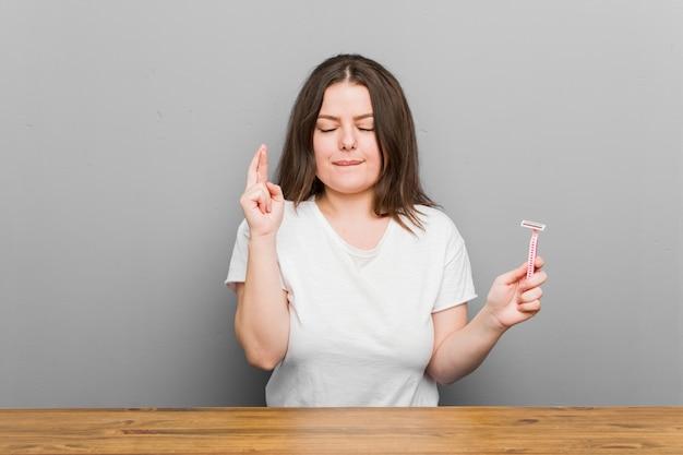 Jeune femme courbée de taille plus tenant une lame de rasoir croisant les doigts pour avoir de la chance