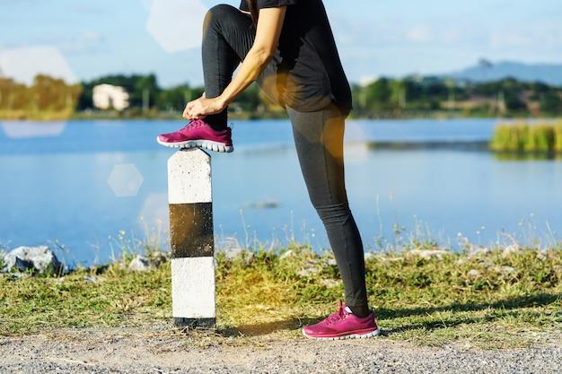 Jeune femme, coureur, attacher, lacets