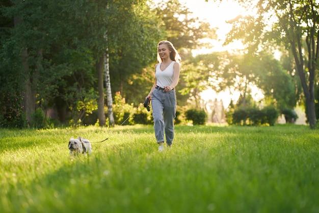 Jeune femme courir avec bouledogue français dans le parc