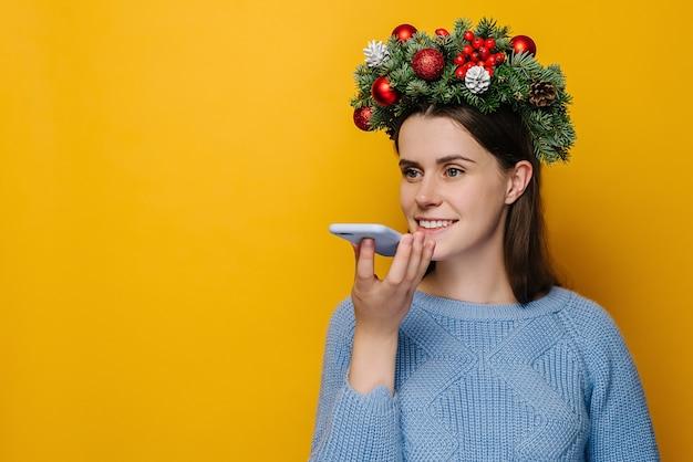 Jeune femme avec une couronne autour de la tête à l'aide de téléphone