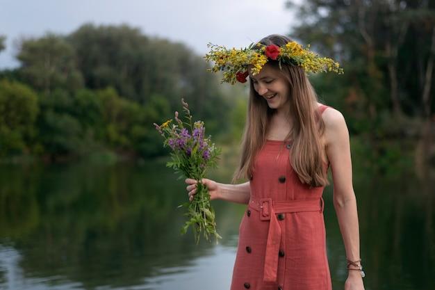 Jeune femme avec une couronne sur la tête avec bouquet de fleurs sauvages