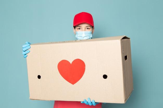 Jeune femme courrier en rose t-shirt casquette rouge tenant la boîte sur le mur bleu