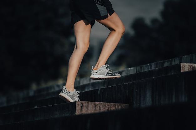 Une jeune femme court en été dans la ville le matin, fond d'escalier