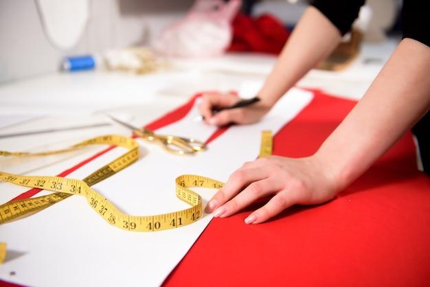 Jeune femme couturière coud des vêtements sur machine à coudre.