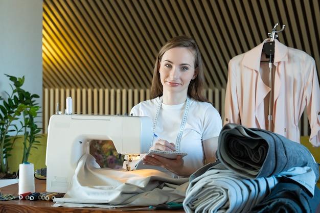 Jeune femme couturière prend des notes sur les mesures des vêtements sur un ordinateur portable dans un atelier de couture
