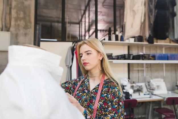 Jeune femme couturière se tient dans un studio bien entretenu et ajuste les vêtements.
