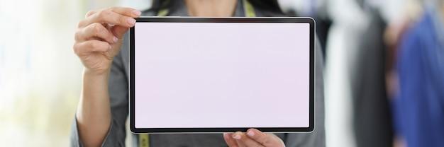 Jeune femme couturière tenant une tablette numérique dans ses mains concept de commandes en ligne en gros plan