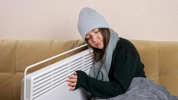 Une jeune femme avec une couverture grise en écharpe et un bonnet tricoté embrasse le radiateur assis sur un canapé moderne et doux dans le salon en hiver froid