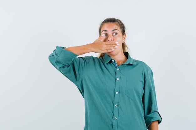 Jeune femme couvrant la bouche avec la main en chemisier vert et à la surprise
