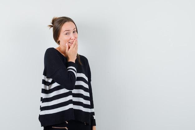 Jeune femme couvrant la bouche avec la main en maille rayée et pantalon noir et à heureux