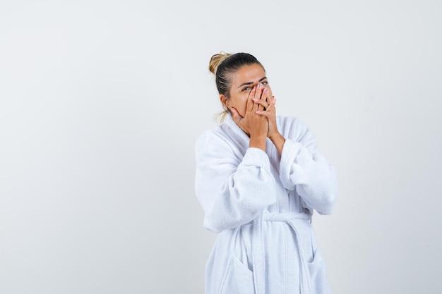Jeune femme couvrant la bouche avec les mains en riant