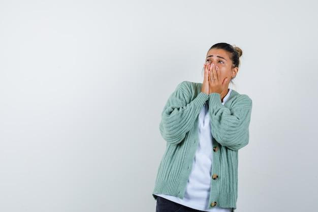 Jeune femme couvrant la bouche avec les mains en t-shirt blanc et cardigan vert menthe et à la surprise