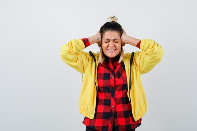 Jeune femme couvrant les oreilles avec les mains en chemise à carreaux, veste et l'air agacée, vue de face.