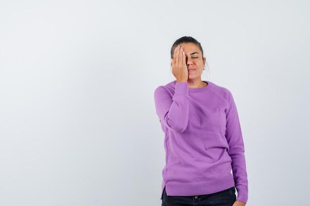 Jeune femme couvrant une partie du visage avec la main et à la grave