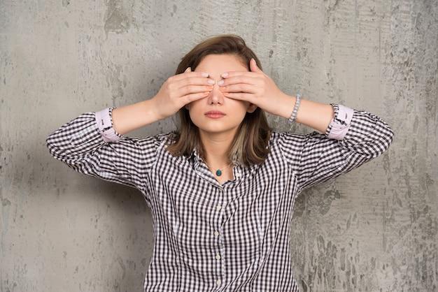 Une jeune femme couvrant ses yeux avec ses mains avec une belle manucure