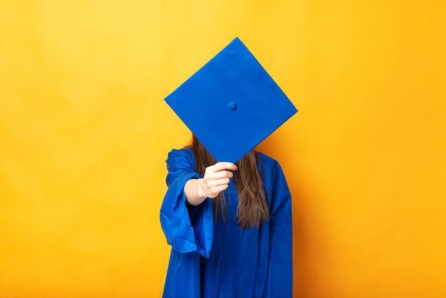 Jeune Femme Couvrant Son Visage Avec Bonnet De Graduation Sur Fond Jaune Photo Premium