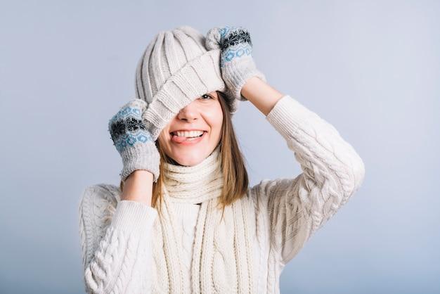 Jeune femme couvrant le visage avec un bonnet clair