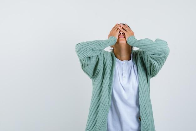Jeune femme couvrant le visage avec les mains en t-shirt, veste et l'air fatigué