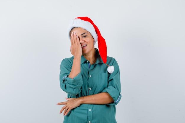 Jeune femme couvrant les yeux avec la main en chemise, bonnet de noel et à la recherche de joie. vue de face.