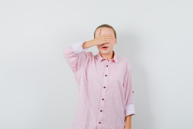 Jeune femme couvrant les yeux avec la main en chemise rose