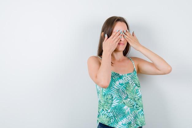 Jeune femme couvrant les yeux avec les mains et semblant excitée, vue de face.