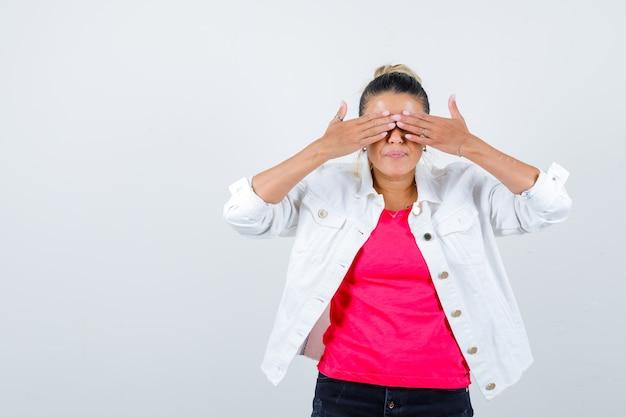 Jeune femme couvrant les yeux avec les mains en t-shirt, veste blanche et semblant ravie, vue de face.