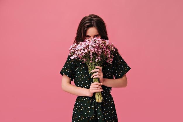 La jeune femme couvre son visage avec un bouquet rose sur isolé